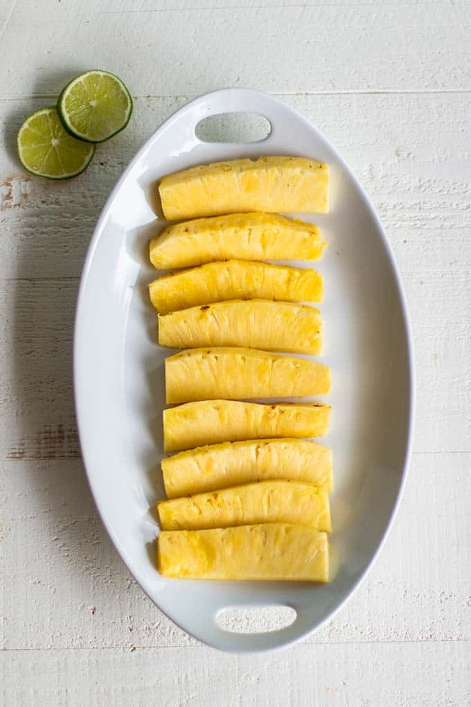 A platter with cut pineapple spears ready to season.