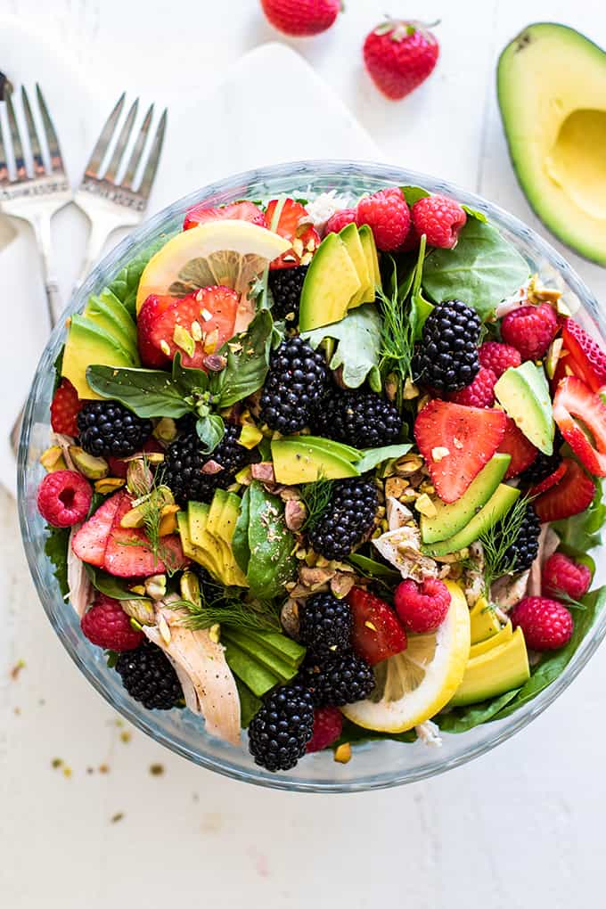 A glass bowl with baby greens as a base for a healthy Whole30 Chicken Blackberry Salad.