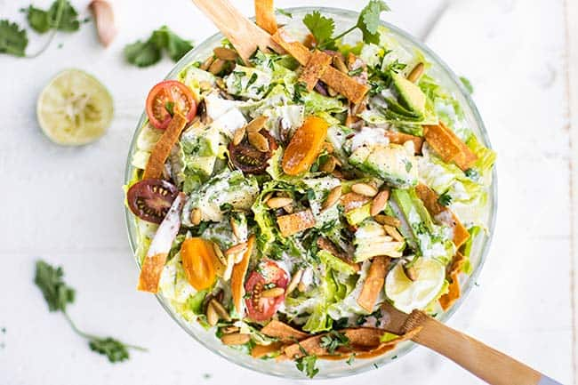 A clear bowl filled with a creamy Mexican caesar salad, with limes and cilantro around the bowl.