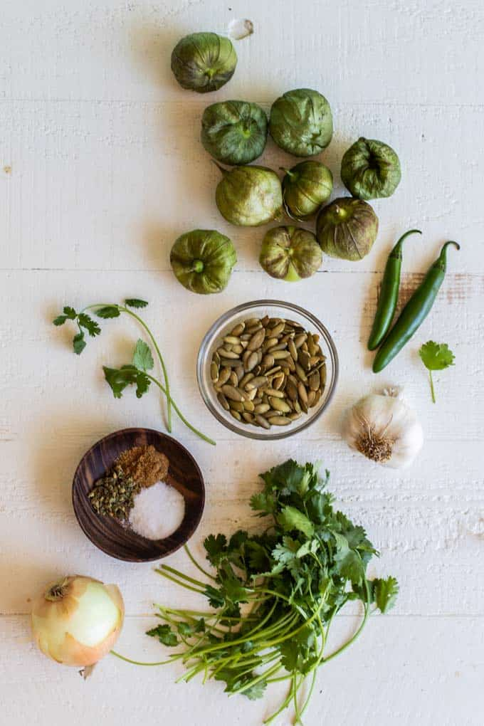 Ingredients for a green mole sauce laid out on a table.