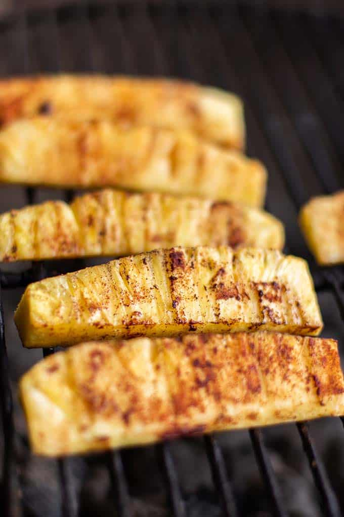 Seasoned pineapple spears on the grill.