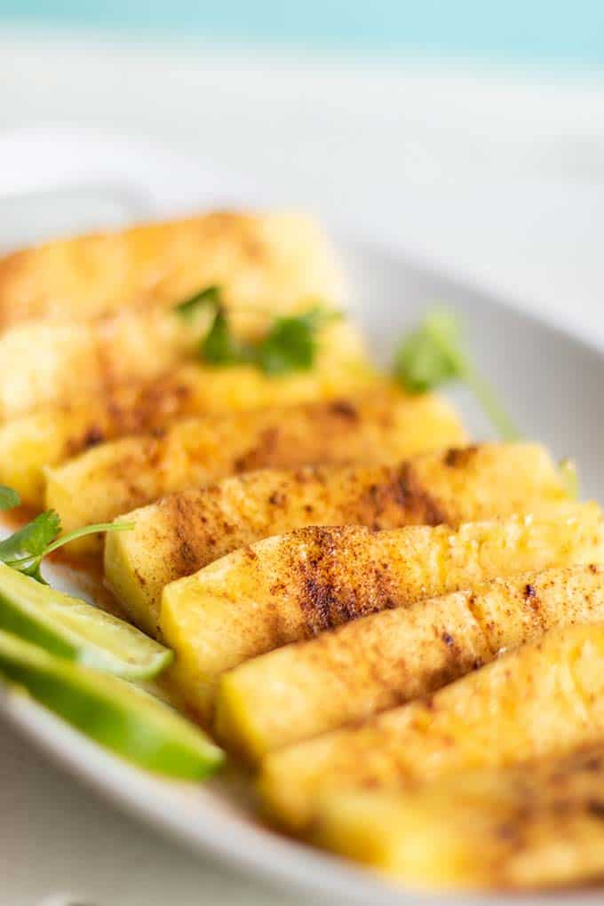 A platter of pineapple being seasoned with cinnamon and chili.