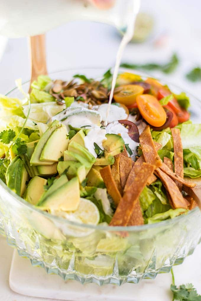 Vegan Caesar salad dressing being poured into a a bowl of salad.