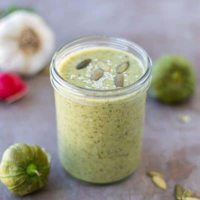 A jar of pipian verde, with tomatillos, garlic, and pumpkin seeds.