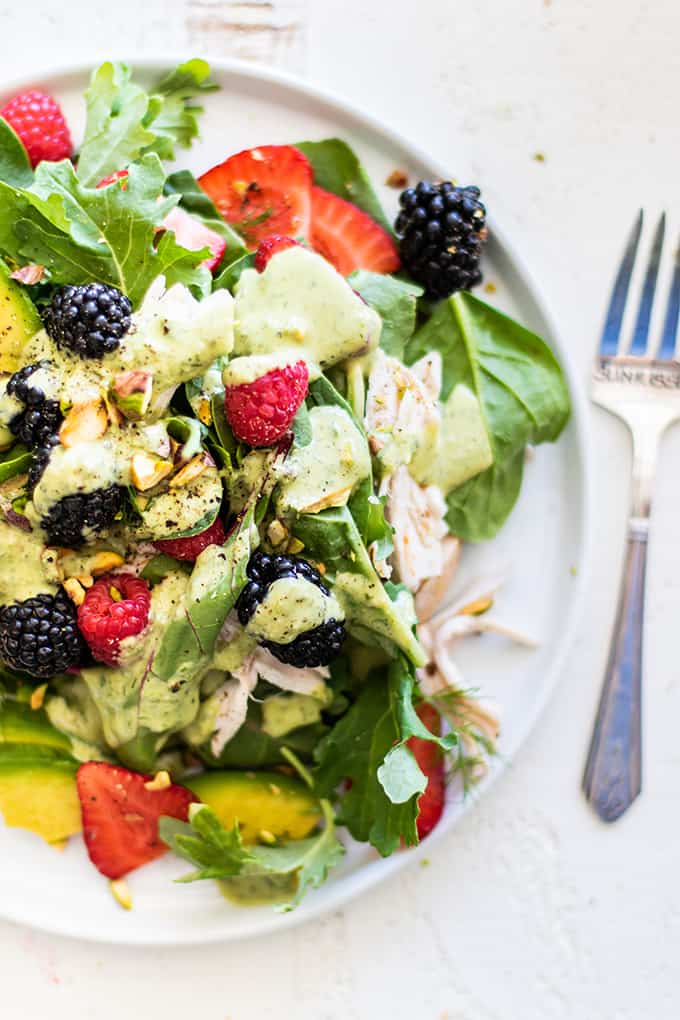 A plate piled high with a chicken blackberry salad drizzled with creamy tahini dressing.
