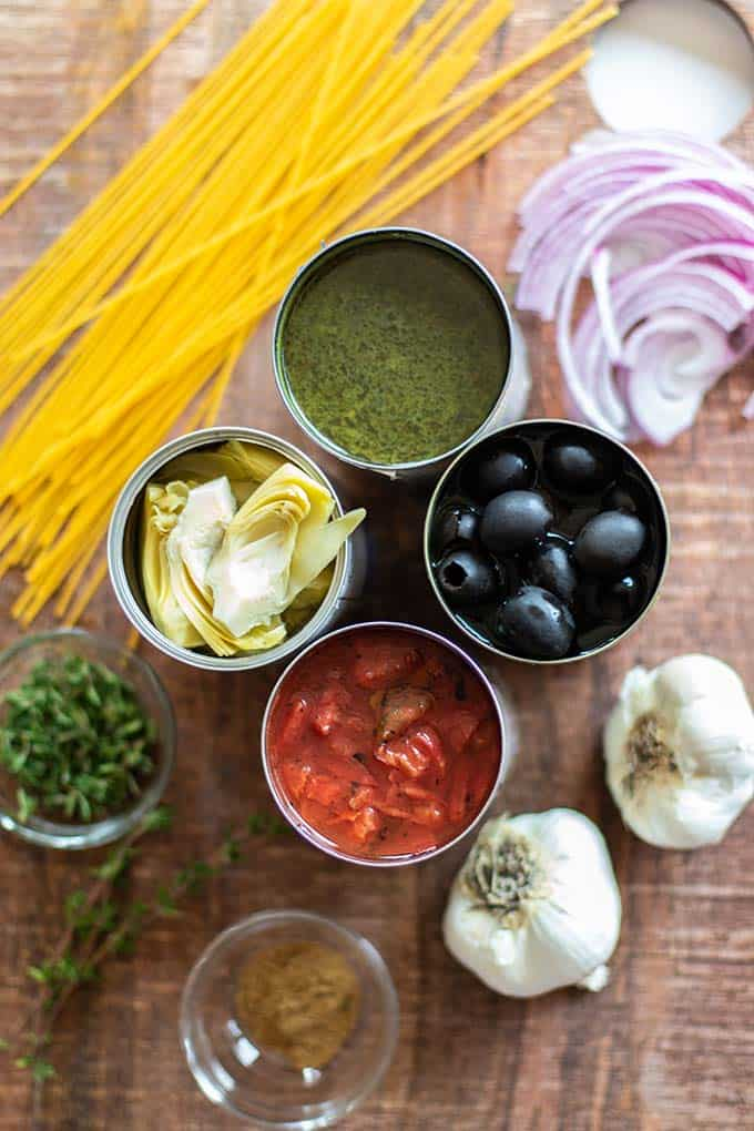A cutting board with the ingredients for Mediterranean One Pot Pasta, including olives, artichokes, and tomatoes.