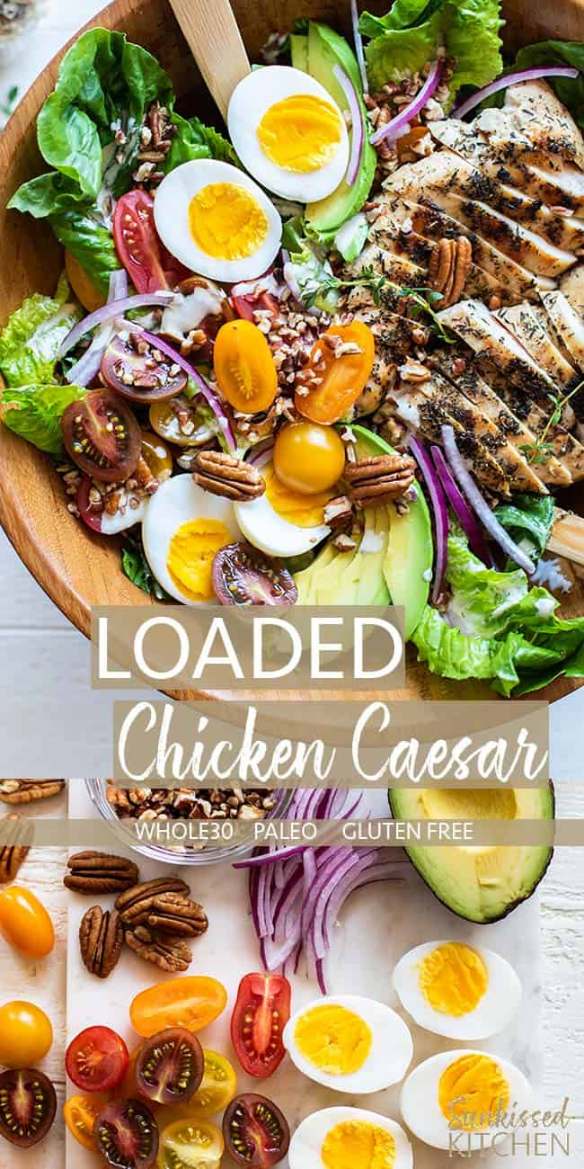 A close up of a loaded whole30 chicken caesar salad, and a cutting board covered in the ingredients for this dish.