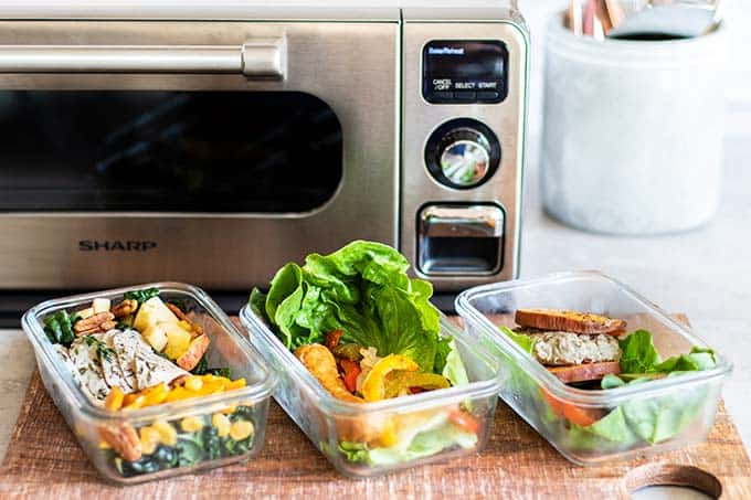 3 Meal prep boxes with a kale salad, sausage lettuce wrap, and turkey burger, all great whole30 lunch options.