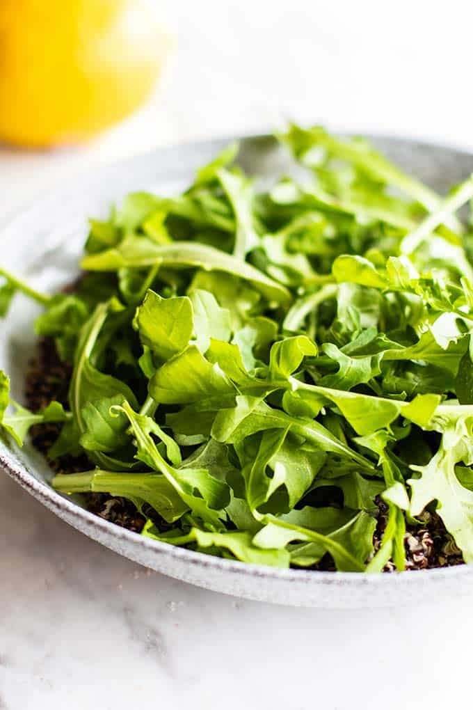 Lots of fresh arugula topping a bed of black quinoa.