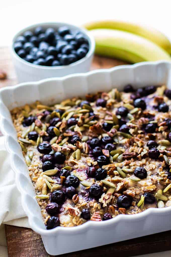 A large dish of healthy baked oatmeal studded with blueberries and pecans.