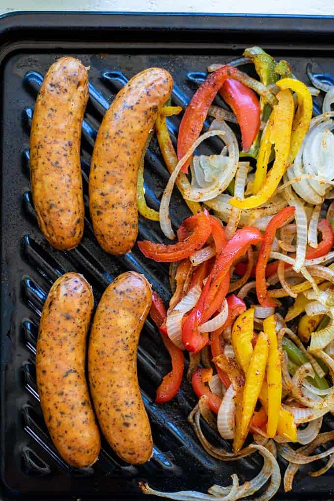 A baking sheet with roasted sausages, peppers, and onions.