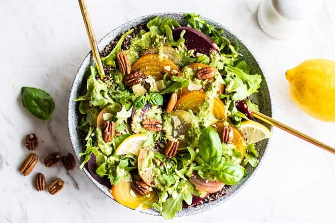 A large bowl of cold beet salad with pecans and lemon next to it.