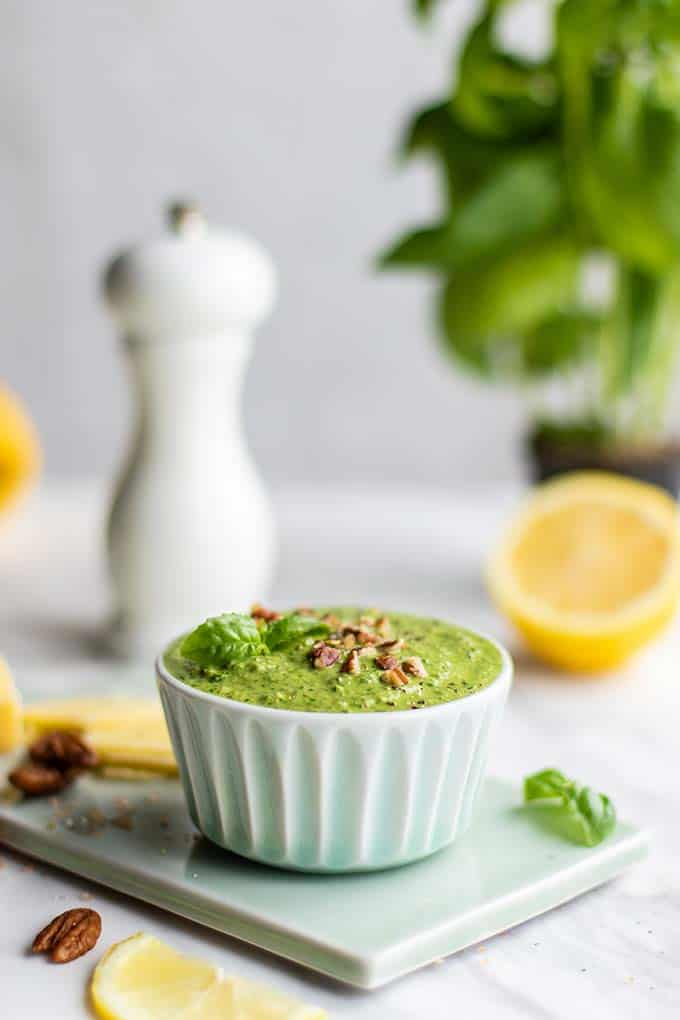 A dish filled with arugula basil pesto garnished with pecans and black pepper.