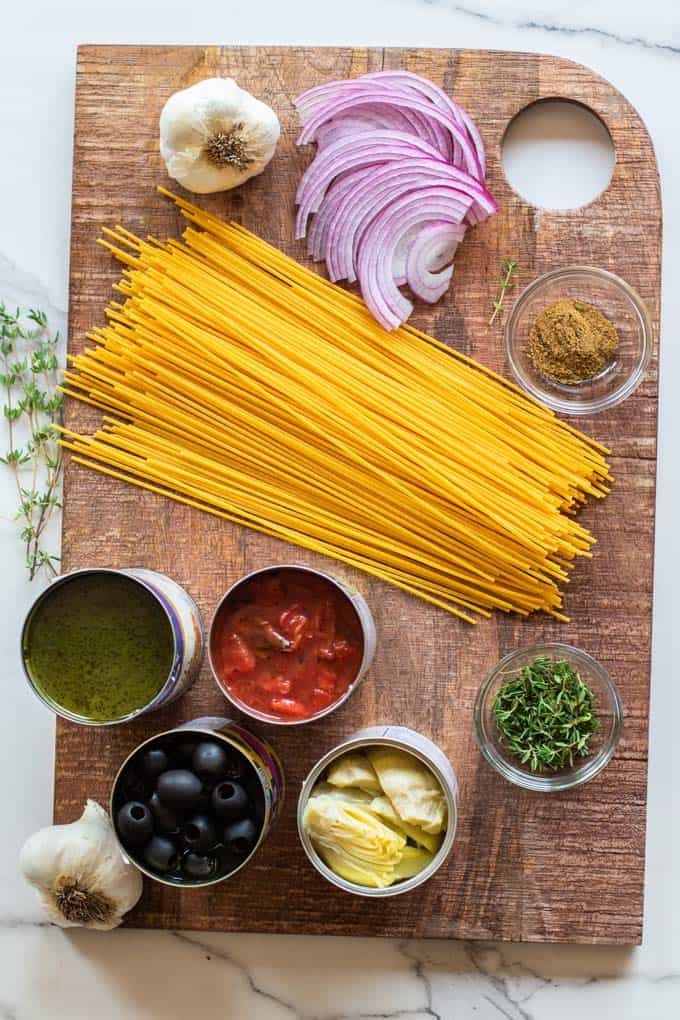 A cutting board with gluten free pasta and other one pot pasta ingredients.