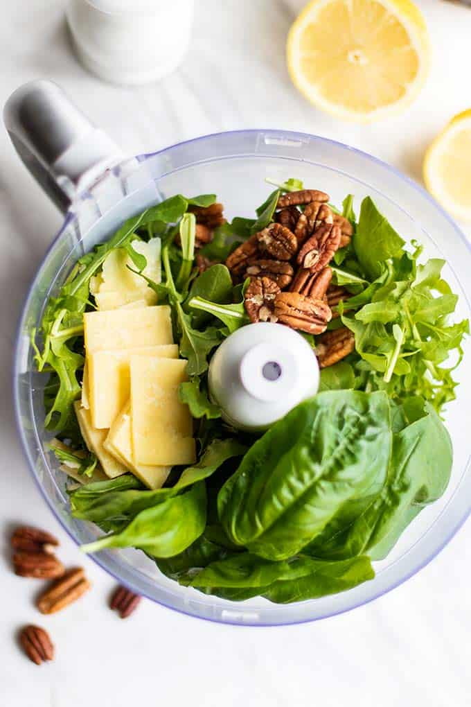 A food processor bowl with arugula, basil, parmesan cheese, and pecans, showing how to make pesto.