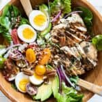 A top view of a crunchy whole30 chicken caesar salad topped with avocado, tomatoes, chicken, eggs and pecans.