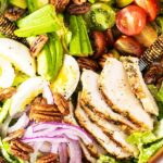 A very close up view of a chicken caesar salad with lots of toppings.