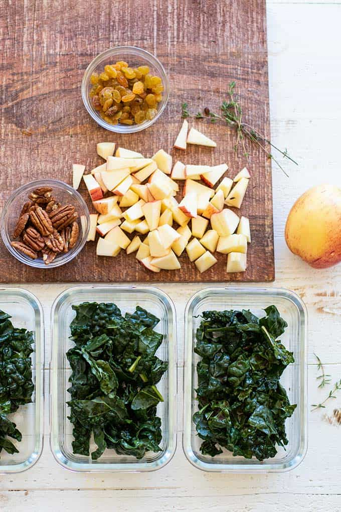 Meal prep containers with massaged kale, next to a cutting board with chopped apples.