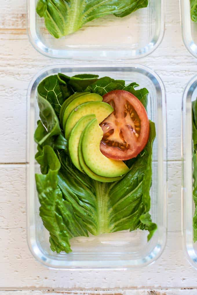 A meal prep container with lettuce, avocado and tomato.