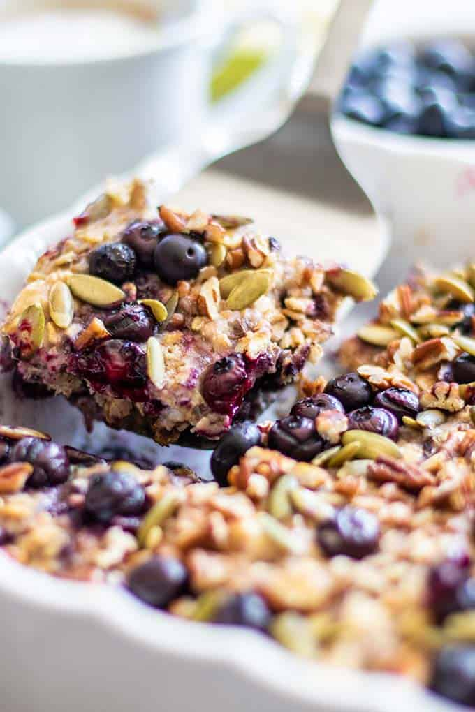 A slice of blueberry baked oatmeal being picked up by a serving spatula.