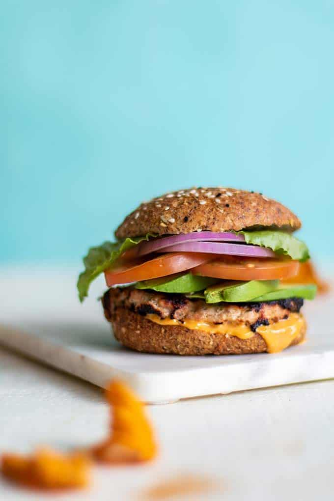 A paleo and gluten free hamburger bun with a turkey burger and toppings.