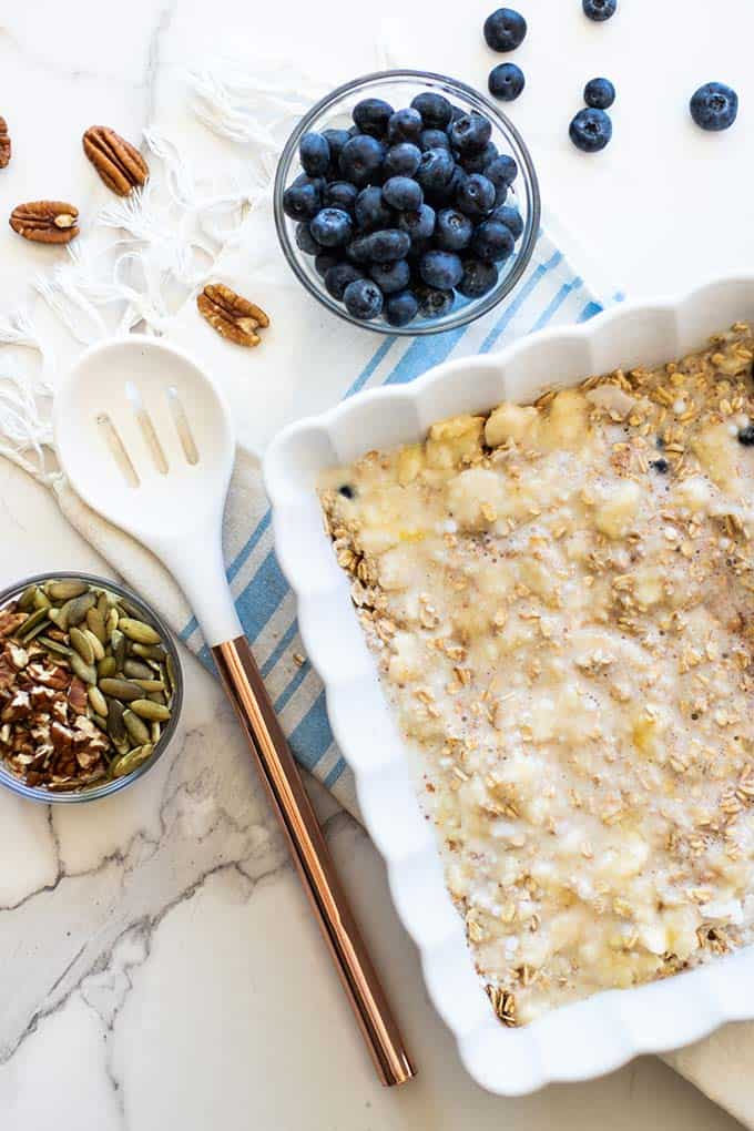 A casserole dish showing how to layer the ingredients in blueberry baked oatmeal.