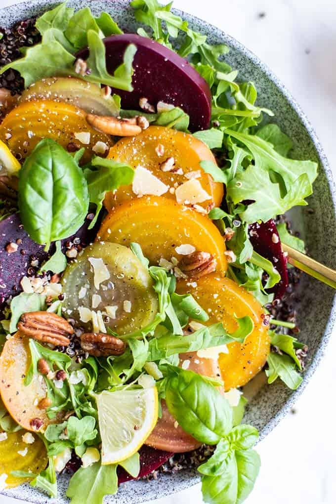 A close up on beets layered on to a quinoa and arugula salad.