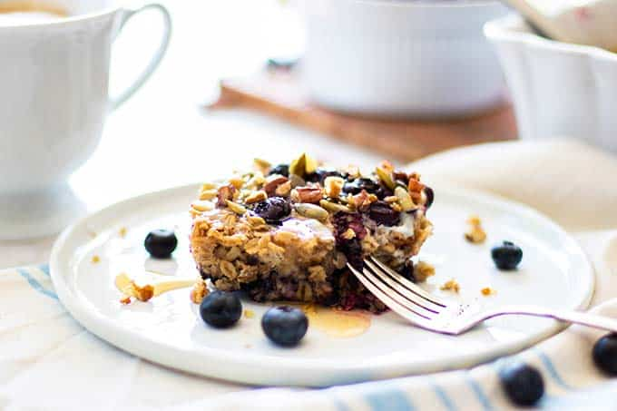 A slice of healthy baked oatmeal topped with honey and a mug of coffee.