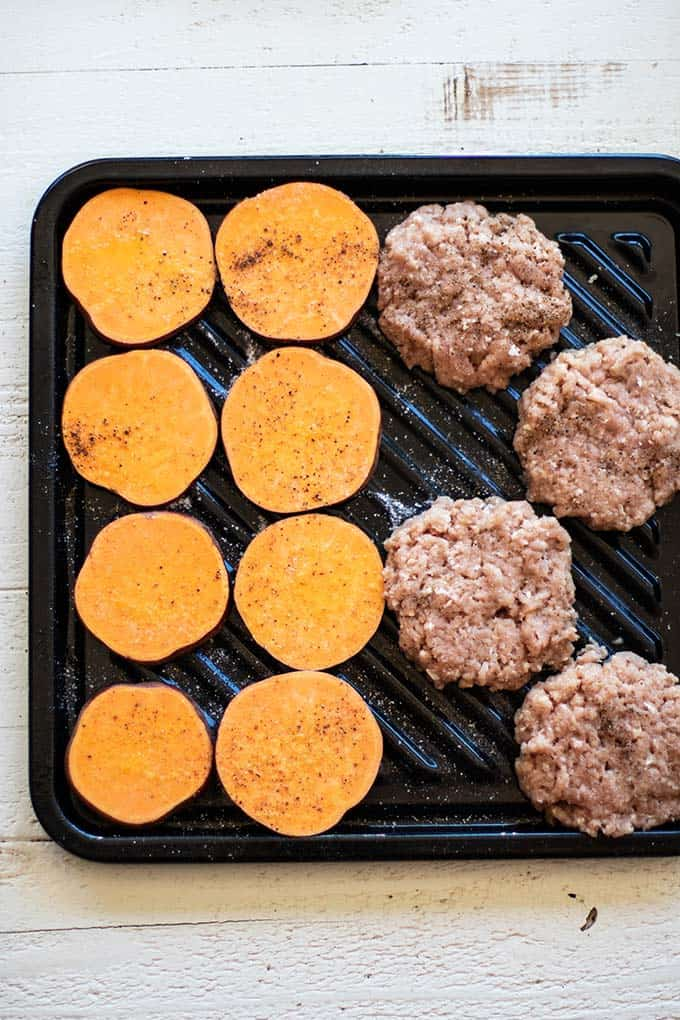 A baking sheet with sweet potato rounds and turkey burgers.