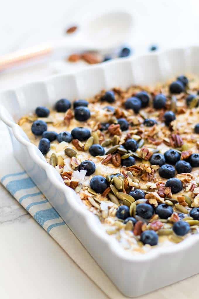A casserole dish filled with blueberries, oatmeal, and a almond milk, egg, and banana mixture.