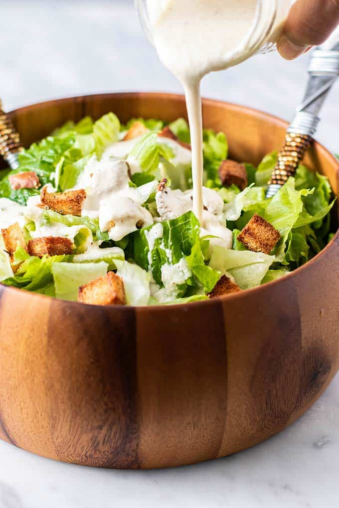 Caesar dressing being poured into a bowl with romaine and croutons.