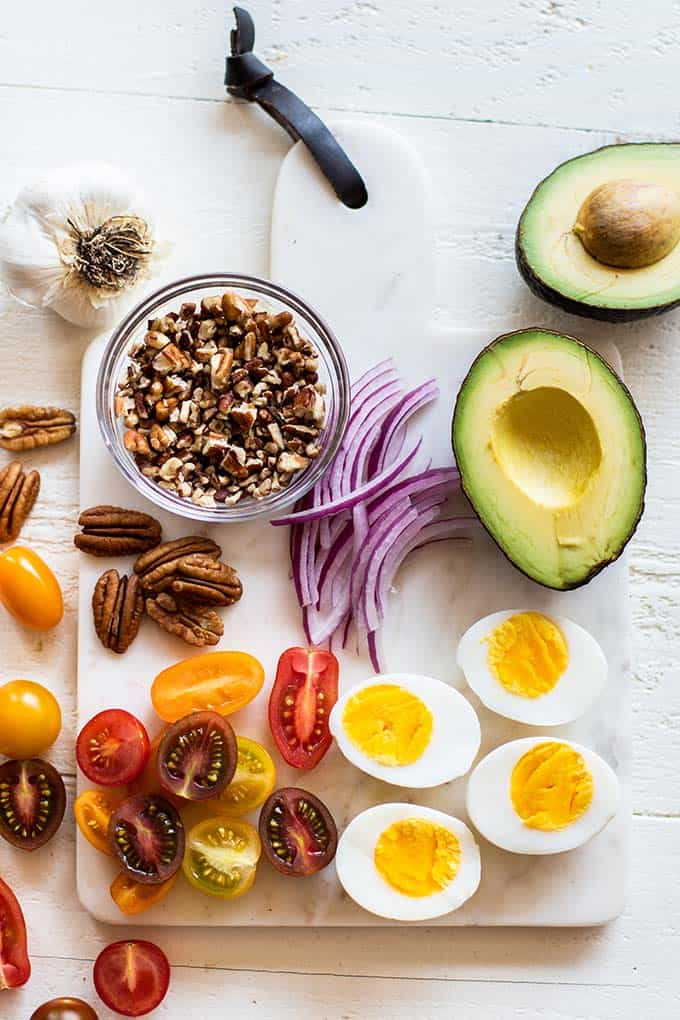 A cutting board with the ingredients for this salad prepared, including avocado, tomatoes, purple onion, eggs, and pecans.
