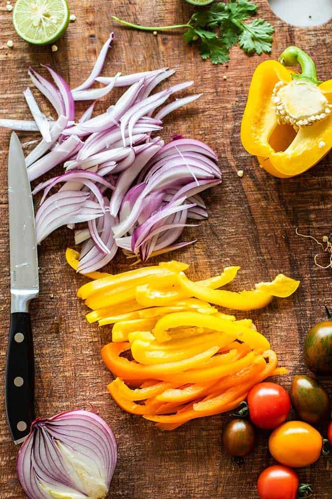 A cutting board with veggies prepared for the Mexican Quinoa dish.