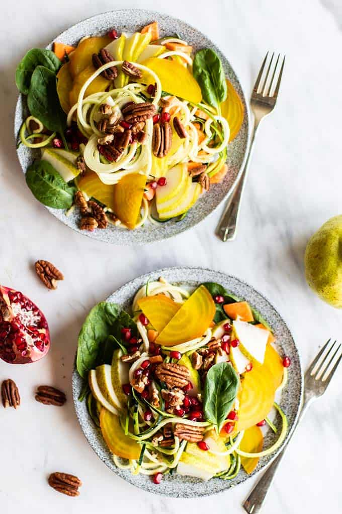 A beautiful zoodle salad topped with pears, pomegranate, and golden beets.