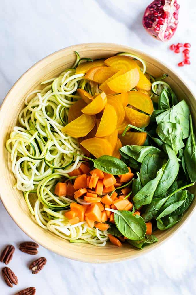 A large bowl with zoodles, spinach, chopped carrots, beefs, and a tahini dressing.