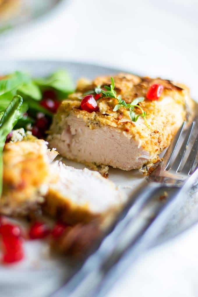 A piece of almond crusted chicken next to an arugula salad garnished with pomegranate seeds.