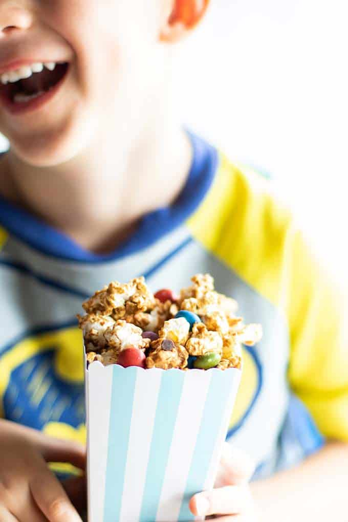 A kid smiling and holding a box of this easy caramel corn recipe.