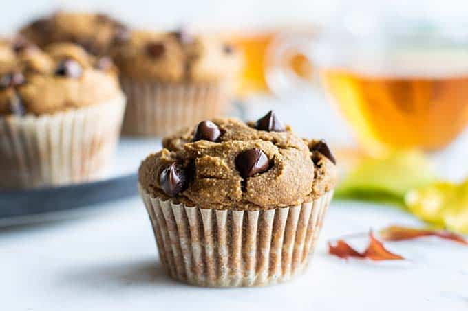 A gluten free pumpkin muffin in front of a cup of tea.