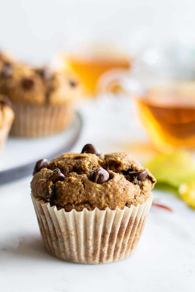 A pumpkin chocolate chip muffin sitting in front of a plate of more muffins.