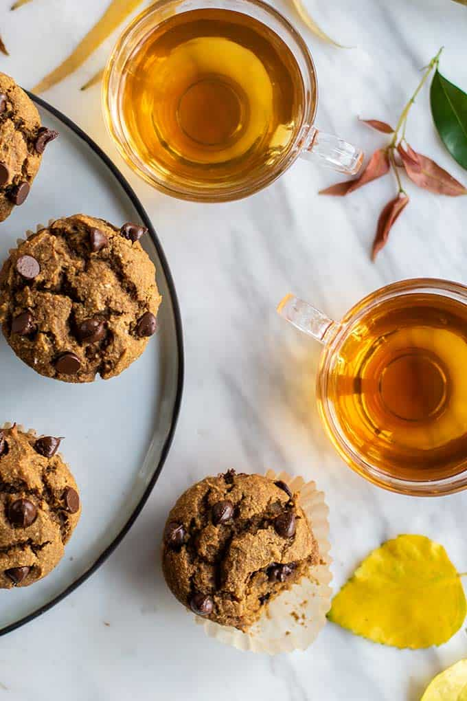 A plate of healthy pumpkin muffins with fall leaves on the table.