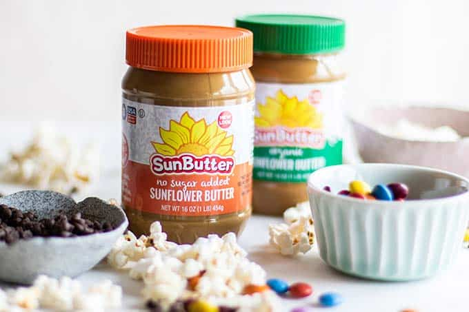 Sunbutter surrounded by popped popcorn, chocolate chips, and candy pieces.