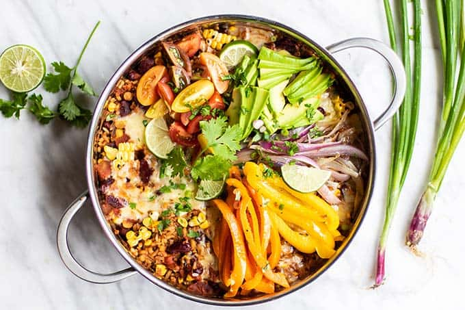 A pan of Mexican Quinoa garnished with cheese, avocado, peppers and onions.