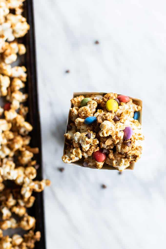 A baking tray with caramel corn, and a popcorn box filled with the treat.