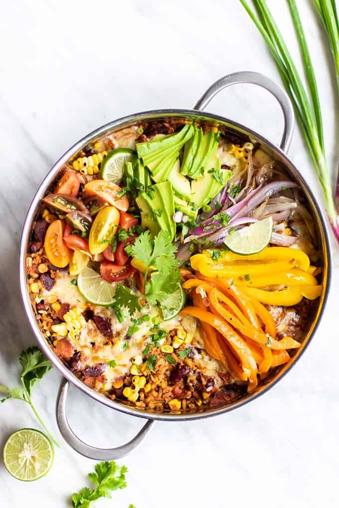 One pan Mexican Quinoa garnished with cheese, avocado, peppers and onions.