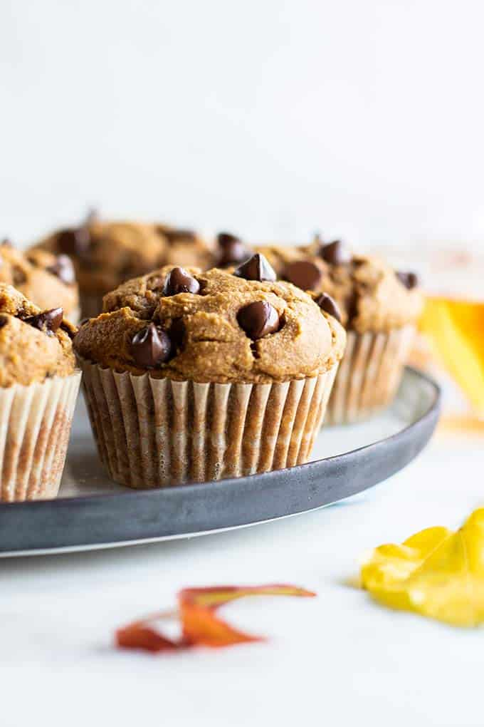Healthy pumpkin muffins on a plate with fall leaves on the table.