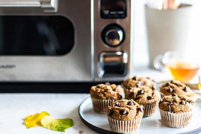 A plate of healthy pumpkin chocolate chip muffins sitting in front of the Sharp Superheated Steam Countertop Oven.