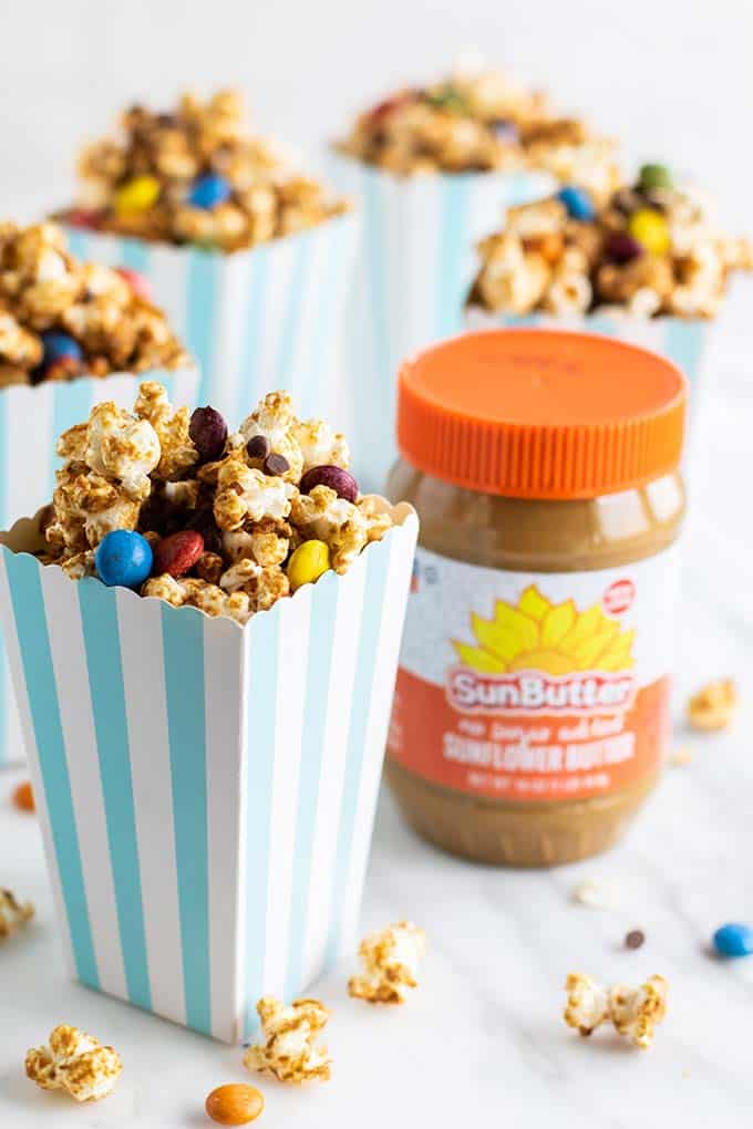 A jar of Sunbutter sitting with popcorn boxes filled with vegan caramel corn.