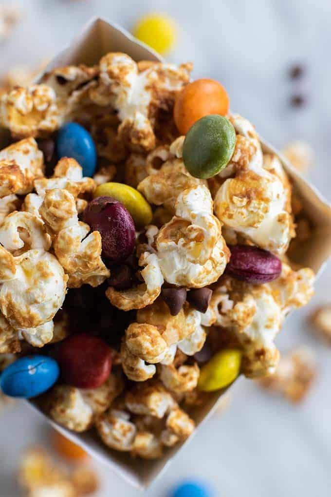 A close up shot of easy caramel corn recipe in a popcorn box.