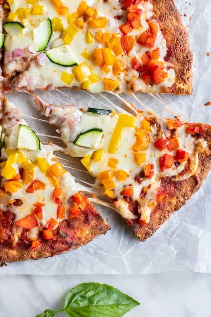 A slice of a veggie pizza built on a paleo pizza crust.