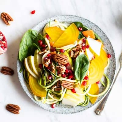 A whole30 zoodle salad topped with pears, pomegranate, beets and pecans.
